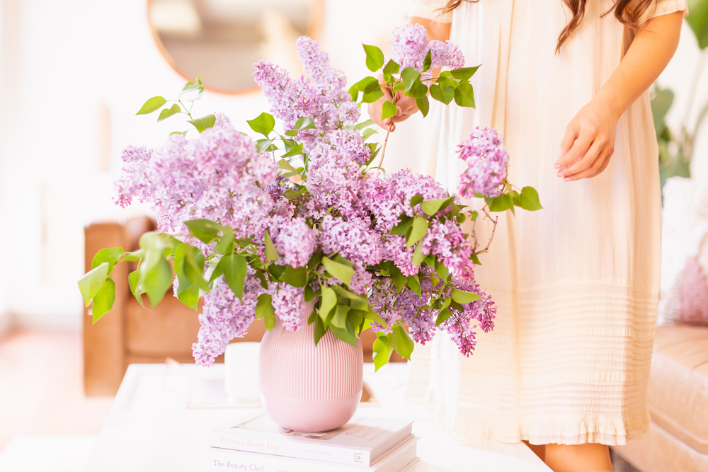 How to Create a Lilac Bouquet | Woman in a flowy linen dress arranging lilac blossoms in her neutral mid century meets boho modern living room | DIY Lilac Flower Arrangement | How to Forage Lilacs | How to Prolong Lilac Vase Life | How to Arrange Lilacs | Fresh Lilac Flower Bouquet | Extremely Pretty Lilac Arrangement | Purple Lilac Arrangement | How to Cut Lilacs from a tree or bush | Calgary Creative Lifestyle Blogger // JustineCelina.com