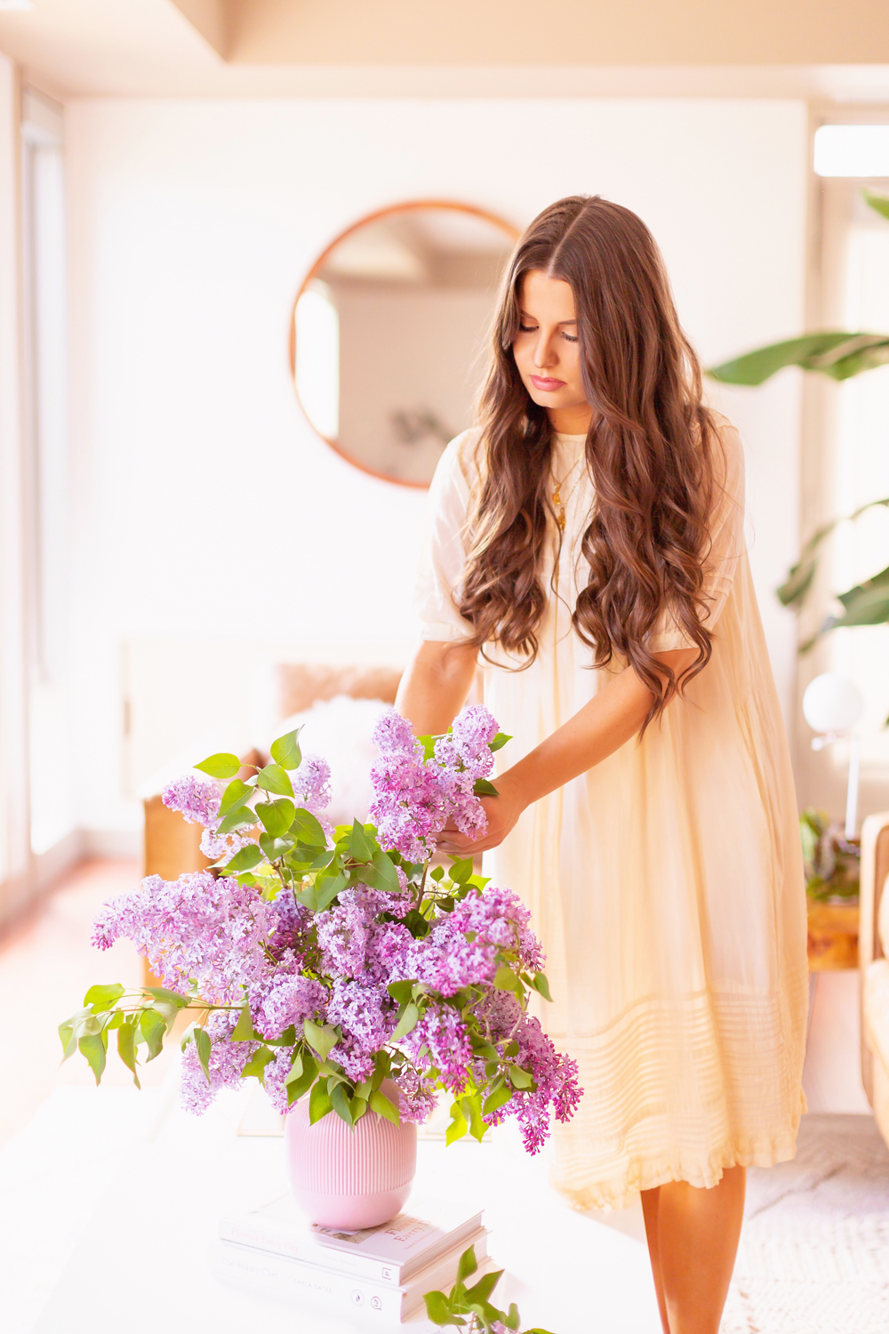 How to Create a Lilac Bouquet | Smiling brunette woman in a flowy linen dress creating an oversized lilac arrangement in her neutral mid century meets boho modern living room | DIY Lilac Flower Arrangement | How to Forage Lilacs | How to Prolong Lilac Vase Life | How to Arrange Lilacs | Fresh Lilac Flower Bouquet | Extremely Pretty Lilac Arrangement | Purple Lilac Arrangement | How to Cut Lilacs from a tree or bush | Calgary Creative Lifestyle Blogger // JustineCelina.com