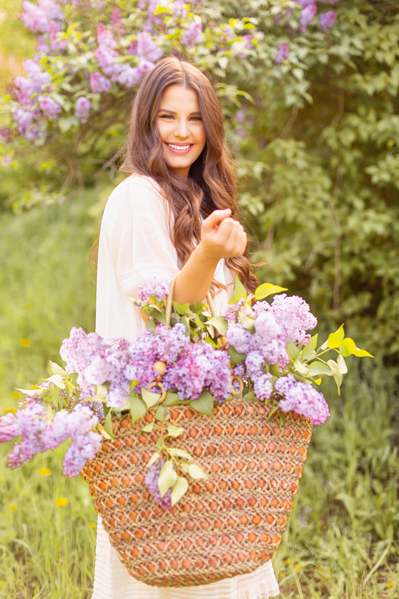 Smiling brunette woman carrying a tote bag of lilac boughs in a flowy linen dress | DIY Lilac Flower Arrangement | How to Forage Lilacs | How to Cut Lilacs from Bush or Tree | How to Prolong Lilac Vase Life | How to Arrange Lilacs | Fresh Lilac Flower Bouquet | Extremely Pretty Lilac Arrangement | Purple Lilac Arrangement | How to Cut Lilacs from a tree or bush | Calgary Creative Lifestyle Blogger // JustineCelina.com