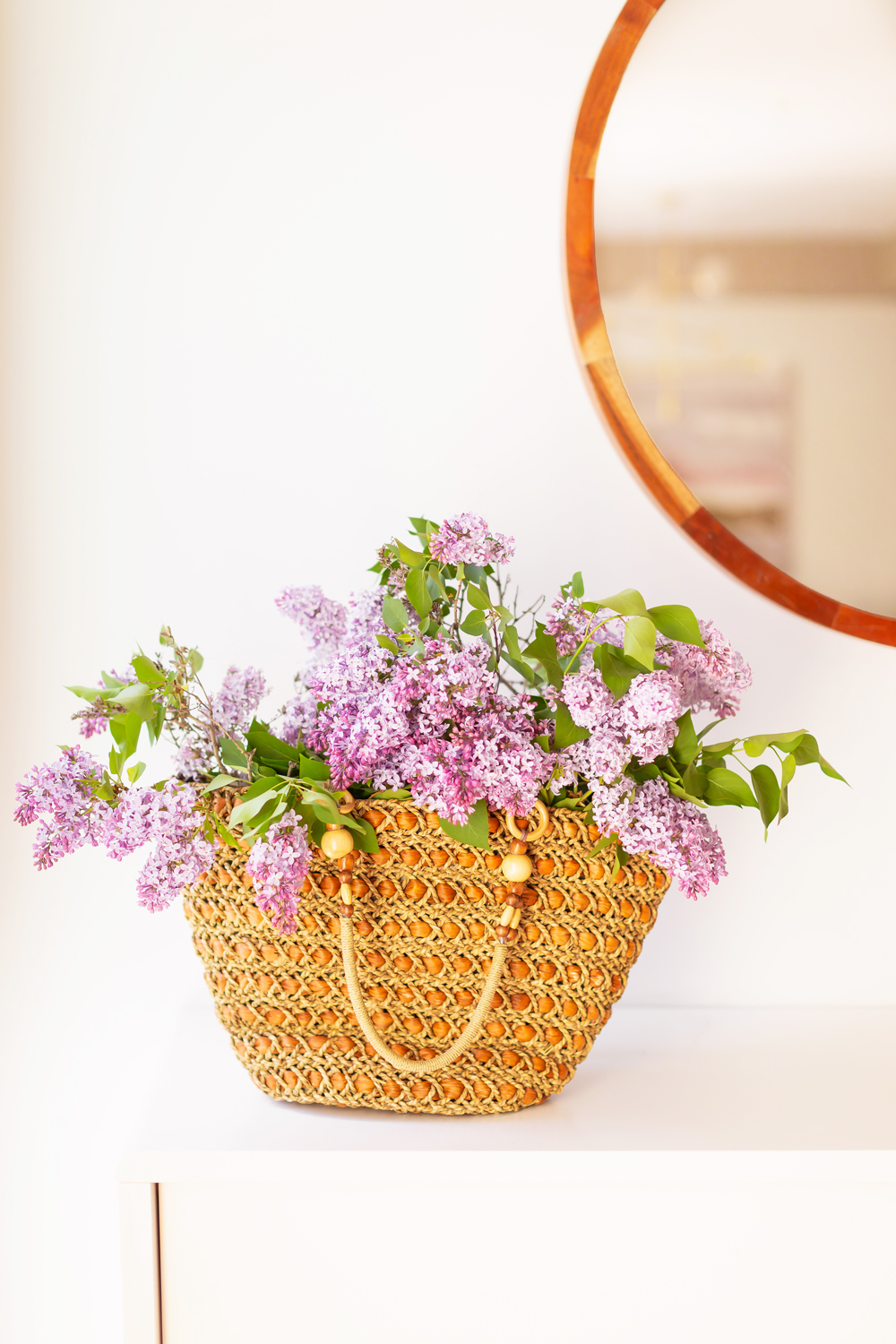 A vintage rattan tote bag overflowing with blooming lilac branches in JustineCelina's light and airy mid century meets boho modern living room | DIY Lilac Flower Arrangement | How to Forage Lilacs | How to Prolong Lilac Vase Life | How to Arrange Lilacs | Fresh Lilac Flower Bouquet | Extremely Pretty Lilac Arrangement | Purple Lilac Arrangement | How to Cut Lilacs from a tree or bush | Calgary Creative Lifestyle Blogger // JustineCelina.com
