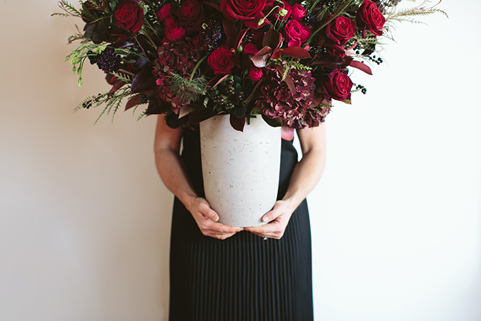 Luxe Holiday Floral Inspiration | Moody Oversized Winter Flower Arrangement in a cement vase with Black MagicRoses, Black Baccara Roses Gem and Lace Spray Garden Roses, Liqustrom, Hypericum, Allium, Lisianthus, Scabiosa, Chocolate Lace, Cotinus, Photina and Grevillea by Rebecca Dawn Design // JustineCelina.com