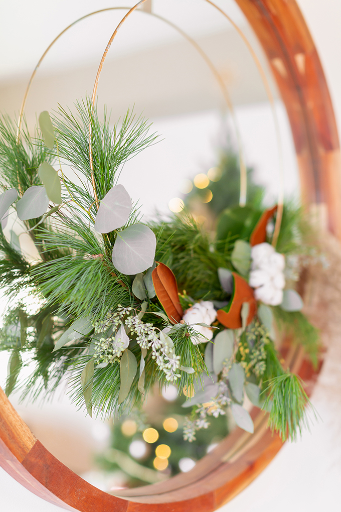 Apartment Friendly Modern Holiday Decor | DIY Modern Holiday Wreath with Magnolia Leaves, Cotton, Silver Dollar Eucalyptus, Seeded Eucalyptus, Cedar and Insense Cedar hung over a round wooden frame mirror | Bohemian, Mid Century Modern Holiday Decor | Bohemian Holiday Home Tour 2018 | Caramel Mid Century Modern Leather Couches | Canadian Tire CANVAS Ornaments // JustineCelina.com