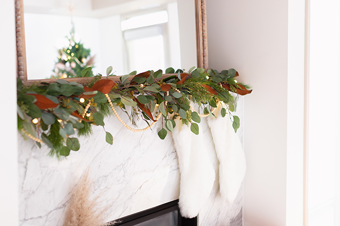 Apartment Friendly Modern Holiday Decor | Canadian Tire CANVAS Pre-lit Eucalyptus Leaves Garland with added greenery, magnolia leaves and wooden beads | Marble Fireplace | Bohemian, Mid Century Modern Holiday Decor | Bohemian Holiday Home Tour 2018 | Caramel Mid Century Modern Leather Couches | Canadian Tire CANVAS Ornaments // JustineCelina.com