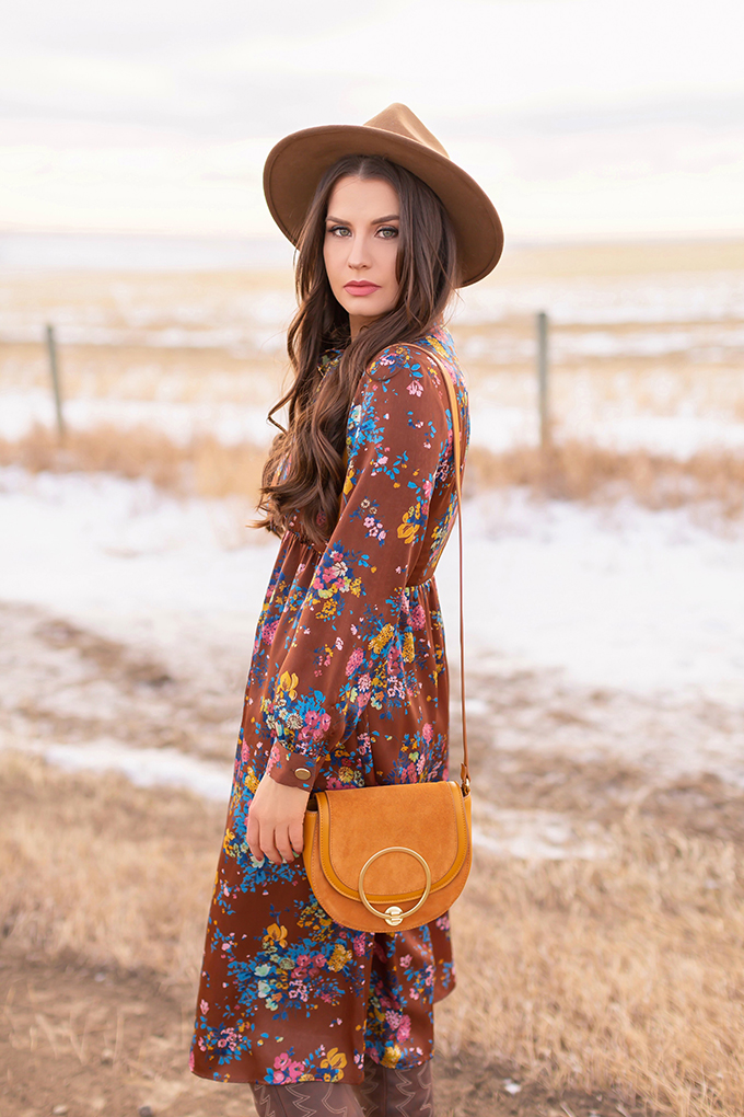Winter 2019 Lookbook | Bohemian Rhapsody: How to Style Midi Dresses for Winter | Brunette Girl Standing in a Country Field at Sunrise Wearing a Brown Floral Dress, Brown Wide Brim Hat and a Mustard Cross Body Bag | Bohemian Winter Style Ideas | Pantone Spring Summer 2019 Fashion Ideas | Calgary, Alberta, Canada Fashion & Lifestyle Blogger // JustineCelina.com