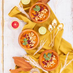 Slow Cooker Vegan Mulligatawny Soup with Red Lentils | #vegan #glutenfree | A warm bowl of vegan mulligatawny soup garnished with roasted cashews, pomegranate arils and cilantro with gold spoons and citrus water | The best vegan mulligatawny soup slow cooker recipe | vegetarian mulligatawny soup | vegetarian mulligatawny soup recipe lentils | vegetarian mulligatawny soup slow cooker | mulligatawny soup crock pot | best winter vegan slow cooker recipes // JustineCelina.com