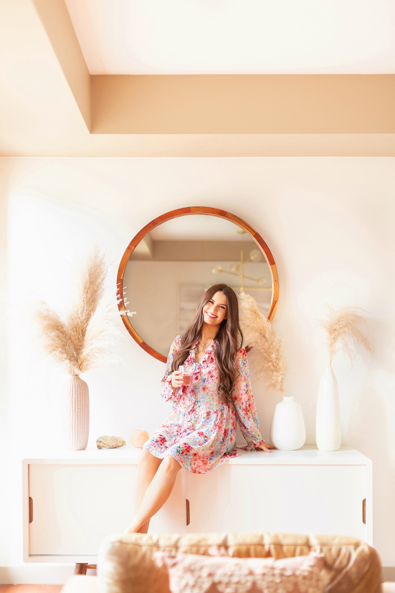 All About Pampas Grass | Pampas Grass Decor | Brunette woman in a bright living room wearing a floral dress drinking a glass of rosé | A Bohemian, Mid-Century Modern Living Room featuring Pampas Grass Dried Decor | Pampas Grass Care and Conditioning | How to Stop Pampas Grass from Shedding | Where to Buy Pampas Grass in Canada 2020 | Where to Buy Pampas Grass in Calgary | Dried Pampas Grass Arrangement Ideas | Bohemian, Mid Century Modern Decor | Calgary Lifestyle Blogger // JustineCelina.com