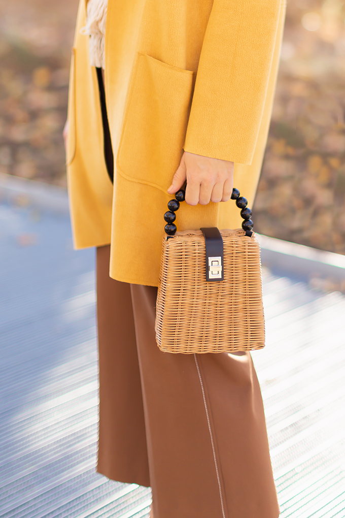 WORK WEAR | SPRING 2019 TRENDS AT THE OFFICE | How to Style Culottes for the Office | Brown 70's Style Culottes with a Mustard Faux Suede Jacket, Knit Fringe Hem Top, Natural Material Zara Rattan Woven Box Bag and Leopard Print D'Orsay Heels | Alex & Ani Hand of Fatima Bracelet | Spring 2019 Trends | Office Appropriate Spring Outfit Ideas // JustineCelina.com