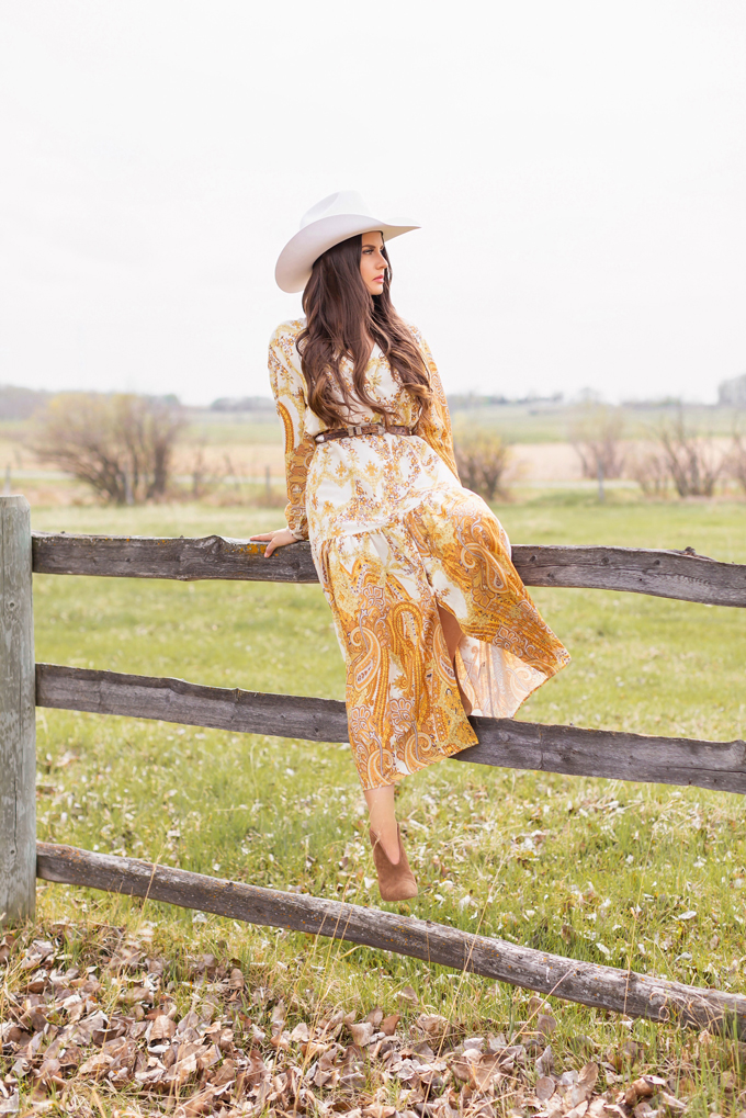 How to Style | Calgary's White Hat for The Stampede | Stampede 2019 Outfit Ideas | Brunette Woman wearing a flow Paisley dress with a vintage western belt, Smithbilt The White Hat in White Felt and mid heel ankle boots with a round rattan bag | Smithbilt White Hat Outfit | How to Style a Cowboy Hat for the Calgary Stampede | Calgary Stampede Dress Code | Bohemian Western Inspired Outfit Summer 2019 | Boho Stampede Style | Justine Celina Maguire x Tourism Calgary // JustineCelina.com