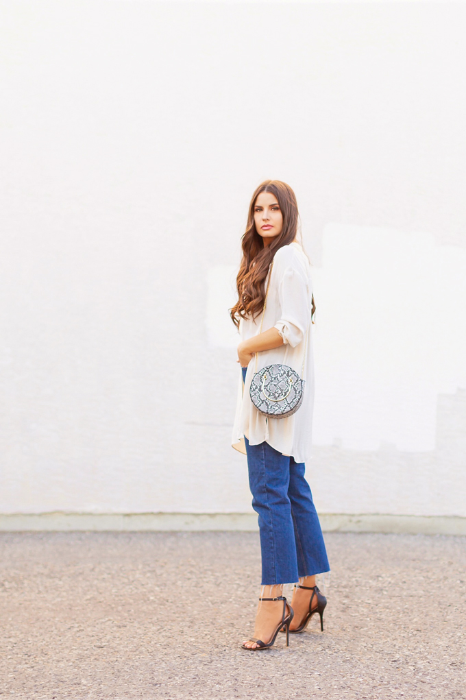 LATE SUMMER 2019 LOOKBOOK | Silk Snakeskin: How to Style Cropped Straight Leg Jeans for Transitional Weather l Summer/Fall 2019 Casual Outfit Ideas | How to style Snakeskin for Autumn 2019 | FreePeople FP One Adella Bralette review | Brunette woman wearing a cropped dark rinse denim, a silk button down shirt, a circular snakeskin bag and black scrappy stiletto sandals | Top Summer to Fall 2019 Transitional Trends and how to wear them | Calgary Fashion Blogger // JustineCelina.com