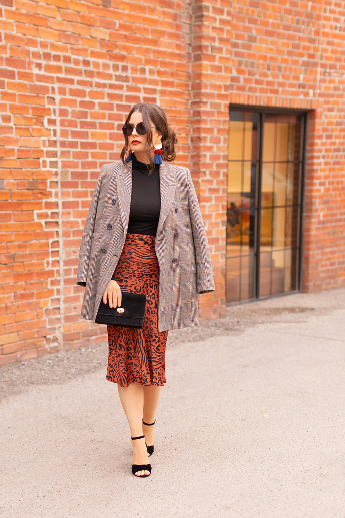 Autumn 2019 Lookbook: Cheetah Chic | Top Fall / Winter 2019 Trends | Top Autumn 2019 Trends and How to Wear Them | Brunette woman wearing a burnt orange cheetah print satin midi skirt, black turtleneck, oversized plaid blazer, black velvet sandals and a vintage suede bag | Chic Fall / Winter 2019 Evening Outfits | How to Style Cheetah Print | How to Style Boyfriend Blazers | How to Mix Prints | Top Calgary Fashion & Creative Lifestyle Blogger // JustineCelina.com