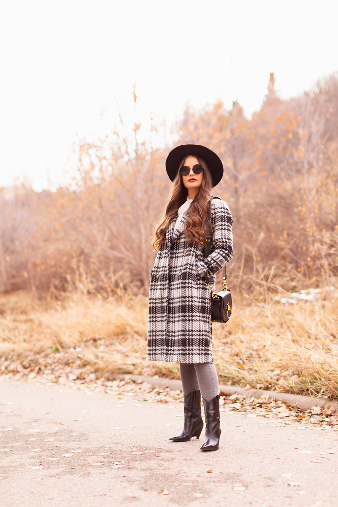 Autumn / Winter 2019 Lookbook: Checked Cowgirl | Top Fall / Winter 2019 / 2020 Trends | Top Winter 2019 Trends and How to Wear Them | Brunette woman wearing a Vero Moda Wool Plaid Coat, Ruffled, Tie Neck Blouse, Grey ripped skinny jeans, Zara Heeled Leather Wedge Cowboy Boots, a black Chloe Tess dupe and a black wide brimmed black hat | Bohemian Canadian Winter Outfit Ideas | Western Winter Outfit Ideas | How to Style a Plaid Coat | Top Calgary Fashion Blogger // JustineCelina.com
