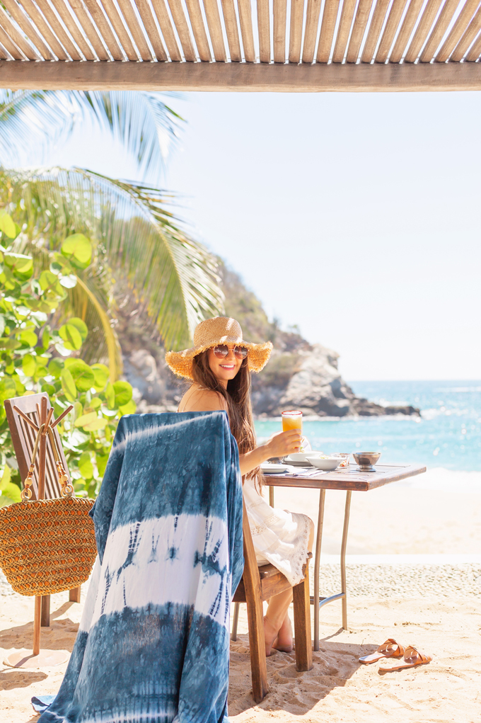 Resort 2020 Lookbook | Tropical Vacation Outfit Ideas | Cute Beach Vacation Outfits 2020 | Mexico Vacation Outfits | What to Wear on Vacation 2020 | How to Style Tie Dye | Pantone 2020 Color of the Year Classic Blue Tie Dye Kimono | Brunette Woman wearing a white bikini cover-up, tie dye kimono and frayed brim straw hat | Camino Real Zaashila, Huatulco 2020 Review | Lunch at Camino Real Huatulco Beach Club 2020 | Tangolunda Bay | Calgary Fashion & Travel Blogger // JustineCelina.com