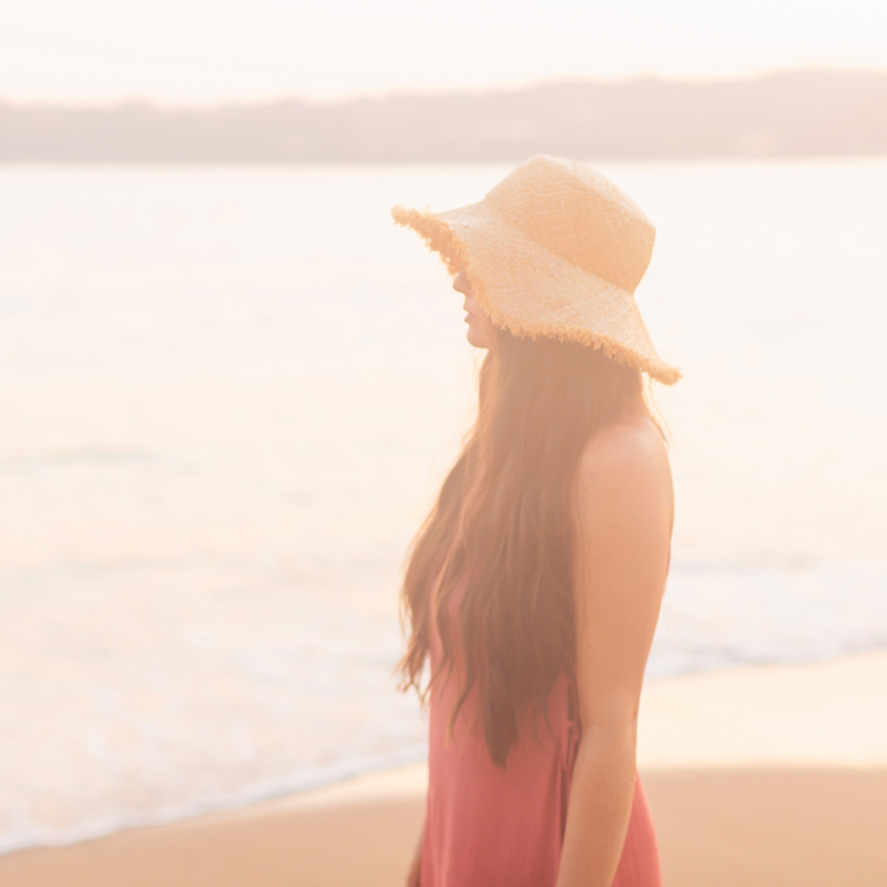 January 2020 Soundtrack | Brunette woman overlooking Tangolunda Bay at Sunset wearing a frayed brim straw hat and a coral dress | Camino Real Zaashila, Huatulco Review | Camino Real Resort Huatulco 2020 | Tangolunda Bay | Calgary Lifestyle, Fashion & Travel Blogger // JustineCelina.com