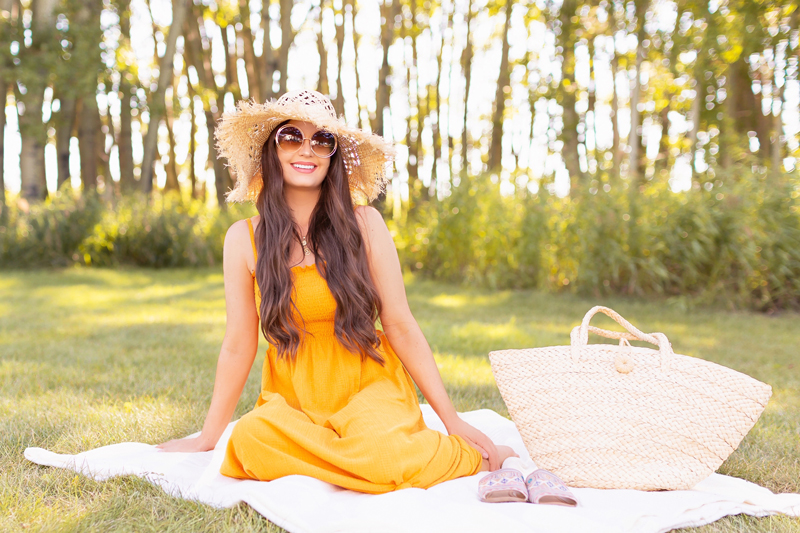 Summer 2020 Lookbook   Boho Summer 2020 Outfit Ideas   Summer Capsule Wardrobe   Summer Quarantine Outfits   Classic Summer Outfit Ideas   The Best Smocked Dresses 2020   The Best Shirred Dresses Summer 2020   The Summer Dresses Under $20   Classic Affordable Summer Style   Summer 2020 Trends   Smiling brunette woman wearing a Dark Yellow H&M Crinkled Dress and round sunglasses sitting on a blanket with a Straw Bag and Colourful Sandals   Calgary Alberta Fashion Blogger // JustineCelina.com