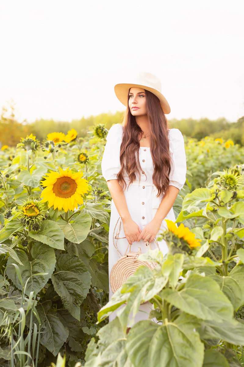 A Guide to Bowden SunMaze & Eagle Creek Farms | Bowden SunMaze September 2020 | Sunflower Field Near Me | The Best Alberta Sunflower Field | Alberta Sunflower U-Pick | Bowden SunMaze Sunflower Field Best Time To Go | Bowden SunMaze Cost | Eagle Creek Farms Review | Sunflower Field Photography Tips | Cottagecore Aesthetic | Brunette woman wearing a cream Crêped Cotton Dress and woven fedora in a field of sunflowers at sunset | Calgary Lifestyle Blogger // JustineCelina.com