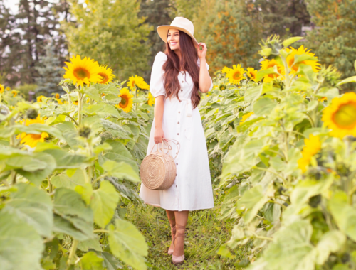 A Guide to Bowden SunMaze & Eagle Creek Farms | Bowden SunMaze September 2020 | Sunflower Field Near Me | The Best Alberta Sunflower Field | Alberta Sunflower U-Pick | Bowden SunMaze Sunflower Field Best Time To Go | Bowden SunMaze Cost | Eagle Creek Farms Review | Sunflower Field Instagram Tips | Cottagecore Aesthetic | Smiling brunette woman wearing a cream Crêped Cotton Dress and woven fedora laughing in a field of sunflowers at sunset | Calgary Lifestyle Blogger // JustineCelina.com