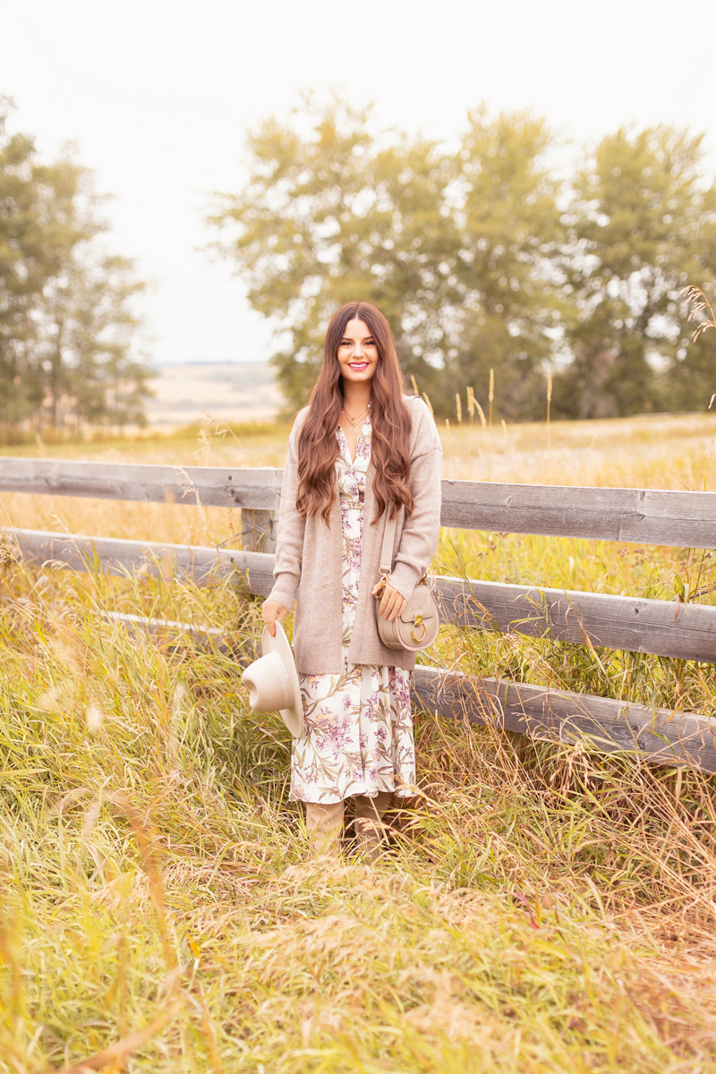Early Autumn 2020 Lookbook | Country Checks | Brunette woman wearing a botanical print button down midi dress, a Chloe Tess Bag in Grey, knee high suede pointed toe boots and a taupe flat brimmed hat next to an weathered fence in the prairies | Boho Fall 2020 Outfit Ideas | Top Fall 2020 Trends | How to Style Midi Dresses for Fall | Bohemian Fall outfit Ideas | How to Wear Florals in Fall | Cottagecore Fall Outfit Ideas | Calgary Alberta Fashion & Lifestyle Blogger // JustineCelina.com