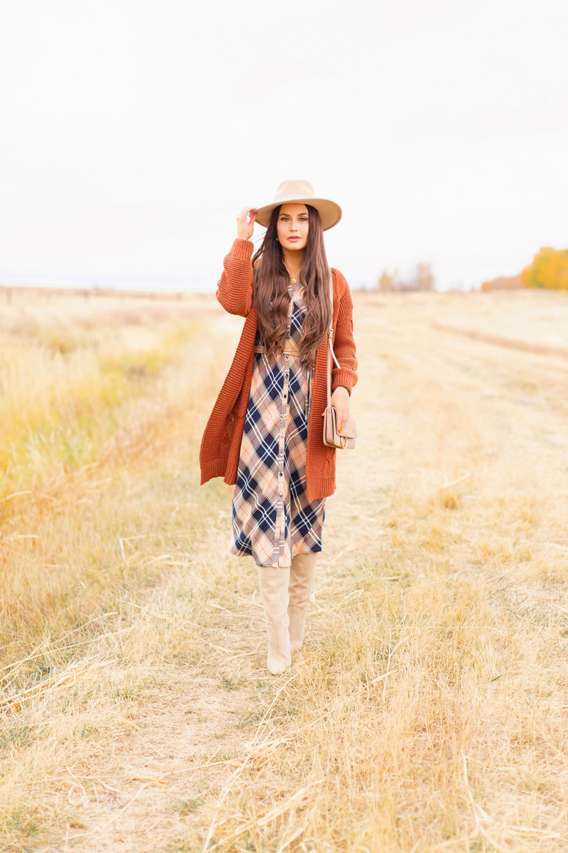 Early Autumn 2020 Lookbook | Brunette woman wearing a taupe flat brimmed fedora, a taupe, rust longline cardigan, orange and navy blue plaid dress, tan crossbody bag and knee high tan suede pointed toe boots | Boho Fall 2020 Outfit Ideas | Top Fall 2020 Trends | Fall on the Alberta Prairies | Thanksgiving Outfit Idea | Bohemian Fall outfit Ideas | Monochromatic Plaid Outfit Ideas | Cottagecore Fall Outfit Ideas | Calgary Alberta Fashion & Lifestyle Blogger // JustineCelina.com