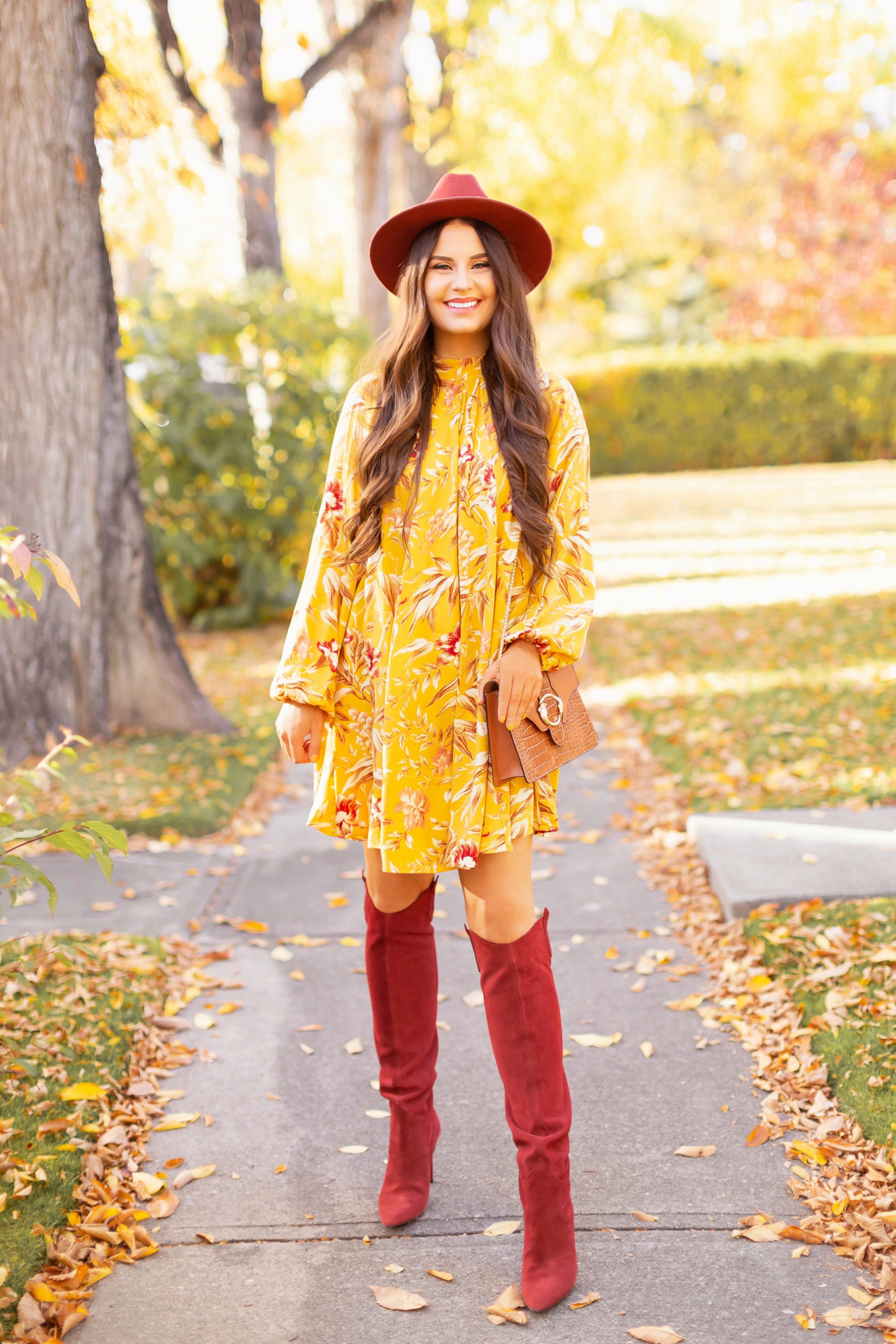 Early Autumn 2020 Lookbook | Mindful Mustard | Smiling brunette woman wearing a rust fedora, a mustard yellow botanical print shift dress, rust knee high western boots and a cognac croc-embossed bag on a sunny autumn afternoon | warm weather fall outfit ideas | Fall 2020 Trend Guide | Casual Fall Fashion | Boho Fall 2020 Outfit Ideas | Fall in Calgary | | Transitional Summer Meets Autumn Fashion | Fall Photoshoot | Calgary Alberta Fashion & Lifestyle Blogger // JustineCelina.com