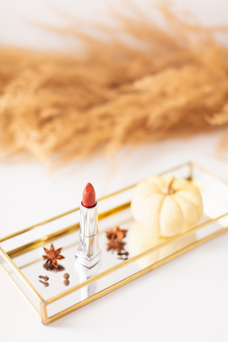 My Top 5 Pumpkin Spice Lipsticks | JustineCelina's favourite fall lipsticks | The Best Pumpkin Spice Lipsticks for Fall | Fall 2020 Lipstick Trends | Lancôme Matte Shaker High Pigment Liquid Lipstick in Abrick Adabra Photos, Review, Swatches | Light / Medium Skintone | The Best Drugstore Fall Lipsticks | The Best Pumpkin Spice Lipsticks for Fall | Lipstick on a Mirrored Tray with spices, a white mini pumpkin and pampas grass in the background | Calgary Beauty Blogger // JustineCelina.com