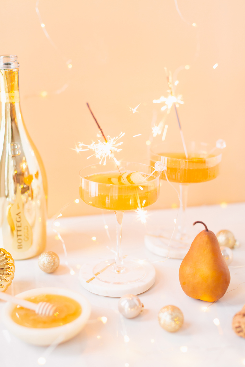 Gilded Vanilla Pear Sparkler | A glitzy, French 75 inspired New Years Eve cocktailfeaturing 24 karat gold infused gin, Bottega Gold Prosecco, Italian vanilla liqueur, lemon juice andHoneyed Vanilla Pear Syrup | Best NYE 2020 cocktails | How to Make sparkling NYE cocktails at home | Champagne cocktail recipe | Champagne Christmas drinks | New Years Eve Sparklers | Refined Sugar Free French 75 | NYE Cocktail Party Recipes | Calgary Creative Lifestyle & Cocktail Blogger // JustineCelina.com