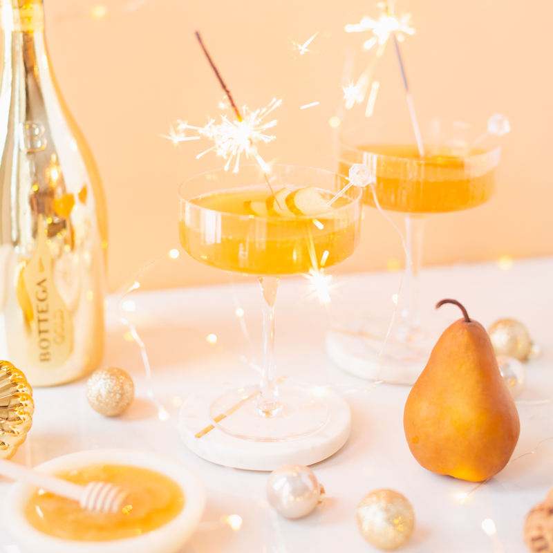 Gilded Vanilla Pear Sparkler | A glitzy, French 75 inspired New Years Eve cocktail featuring 24 karat gold infused gin, Brut Prosecco, Italian vanilla liqueur, lemon juice and Honeyed Vanilla Pear Syrup | Best NYE 2020 cocktails | How to Make sparkling NYE cocktails at home | Champagne cocktail recipe | Champagne Christmas drinks | New Years Eve Sparklers | Modern Refined Sugar Free French 75 | NYE Cocktail Party Recipes | Calgary Creative Lifestyle & Cocktail Blogger // JustineCelina.com