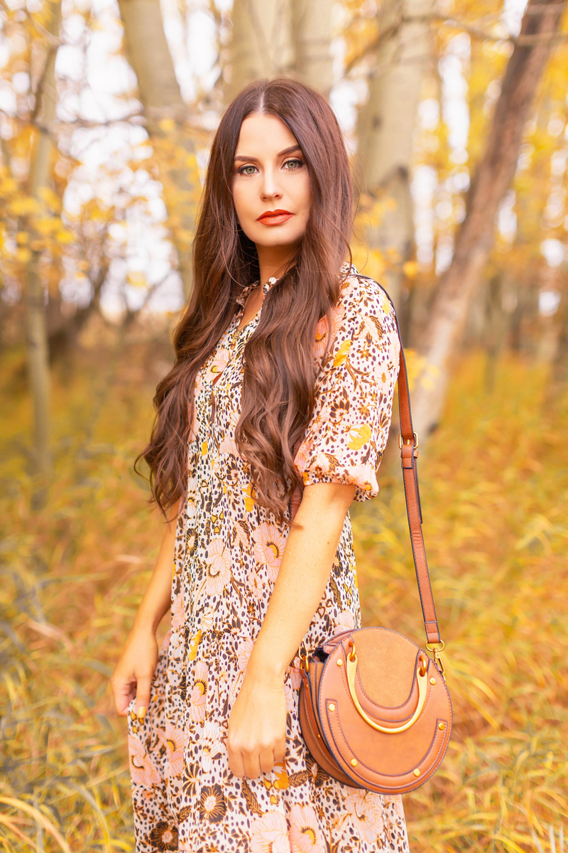 Fall 2020 Lookbook | A Lesson in Layering | Brunette woman wearing a fall floral midi dress, and a round cognac crossbody bag amongst fall leaves | Boho Fall 2020 Outfit Ideas | Top Fall / Winter 2020 Trends | Fall on the Alberta Prairies | Bohemian Fall / Winter outfit Ideas | Cottagecore Fall / Winter Outfit Ideas | How to Style Midi Dresses into Fall and Winter | Creative Layering Ideas | The Best Midi Dresses for Fall | Calgary Alberta Fashion Blogger // JustineCelina.com