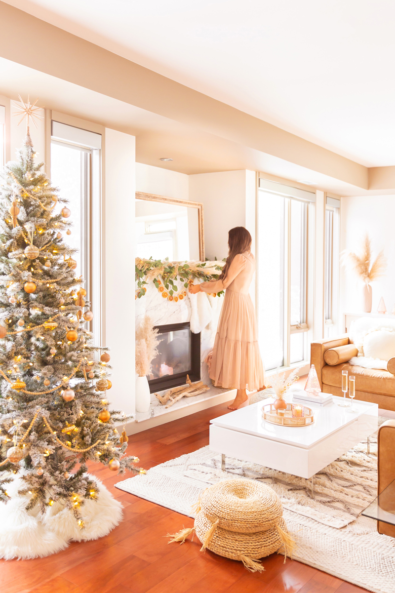 Mid Century Meets Boho Holiday Decor   Brunette woman wearing a taupe chiffon maxi dress hanging stockings in a bright and airy bohemian living room decorating for Christmas   Flocked Christmas Tree with Wood Garland, Metallic and Wood Ornaments   Bohemian Holiday Home Tour 2020   Boho Chic Christmas Decor   DIY boho dried orange garland   Glam neutral holiday decor   Pampas Grass holiday decor   Pampas Grass Garland   Boho Christmas Tree   Canadian Tire CANVAS Ornaments // JustineCelina.com
