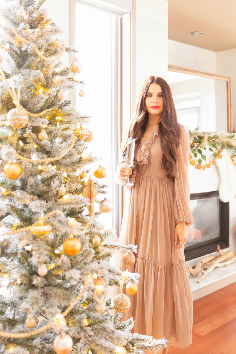 Mid Century Meets Boho Holiday Decor   Brunette woman wearing a taupe chiffon maxi dress and red lipsticks bright and airy bohemian living room holding a flute of champagne   Flocked Christmas Tree with Wood Garland, Metallic and Wood Ornaments   Bohemian Holiday Home Tour 2020   Boho Chic Christmas Decor   DIY boho dried orange garland   Glam neutral holiday decor   Pampas Grass holiday decor   Pampas Grass Garland   Boho Christmas Tree // JustineCelina.com