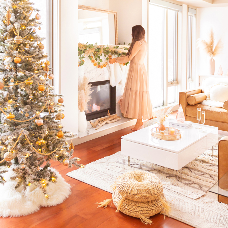 Mid Century Meets Boho Holiday Decor | Brunette woman wearing a taupe chiffon maxi dress hanging stockings in a bright and airy bohemian living room decorating for Christmas | Flocked Christmas Tree with Wood Garland, Metallic and Wood Ornaments | Bohemian Holiday Home Tour 2020 | Boho Chic Christmas Decor | DIY boho dried orange garland | Glam neutral holiday decor | Pampas Grass holiday decor | Pampas Grass Garland | Boho Christmas Tree | Canadian Tire CANVAS Ornaments // JustineCelina.com
