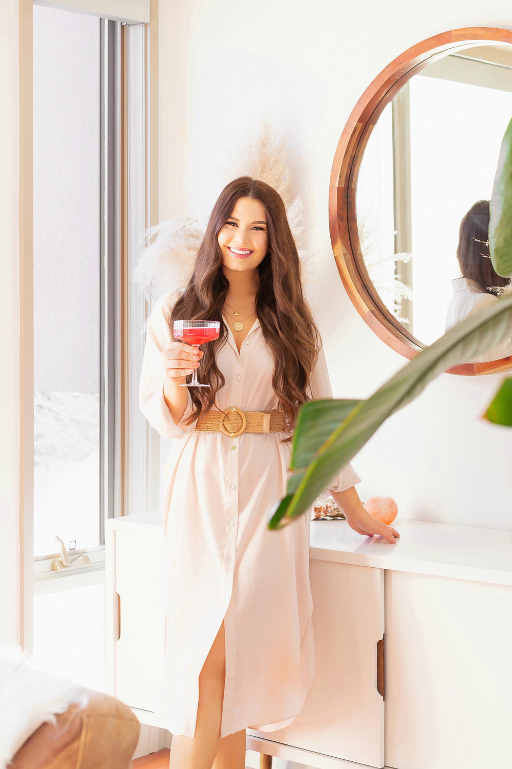 Brunette woman holding a champagne coupe of watermelon kombucha in a bright and airy living room | Calgary Lifestyle Blogger // JustineCelina.com