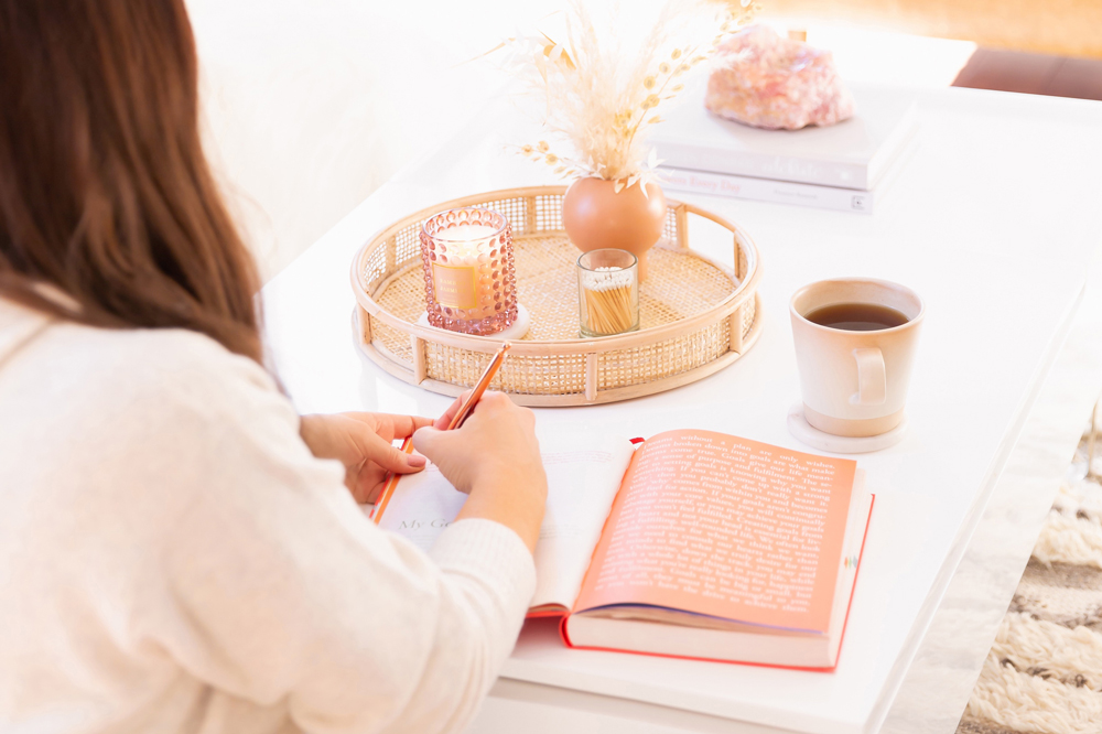 Woman journalling on a coffee table with a candle and cup of coffee in a bright and airy living room | Calgary Lifestyle Blogger // JustineCelina.com