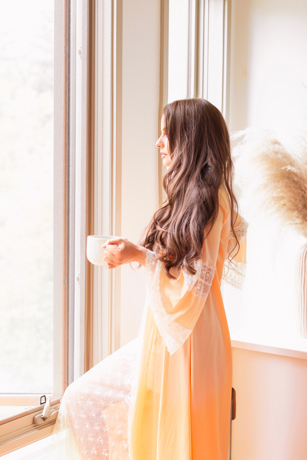 Brunette woman wearing a vintage dressing gown holding a mug of tea in bright and airy boho living room | Calgary Lifestyle Blogger // JustineCelina.com