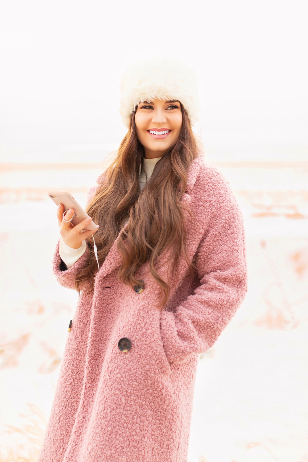 Smiling brunette woman wearing a pink teddy coat listening to an audiobook on a winter walk | Calgary Lifestyle Blogger // JustineCelina.com