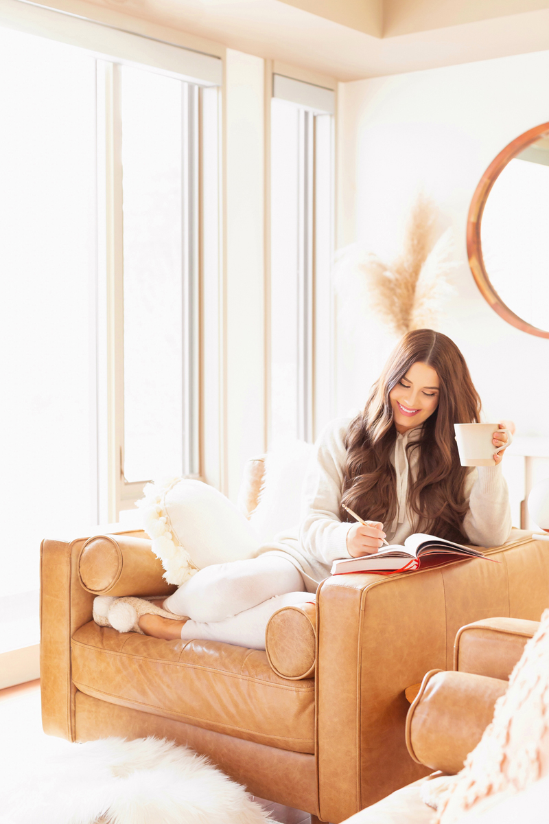 Smiling brunette woman sitting in a mid century leather chair journalling with cup of coffee in a bright and airy boho living room | Calgary Lifestyle Blogger // JustineCelina.com