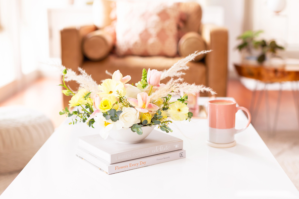 Easter flowers with pampas grass on white coffee table with a pink mug in bright and airy boho living room | Calgary Lifestyle Blogger // JustineCelina.com