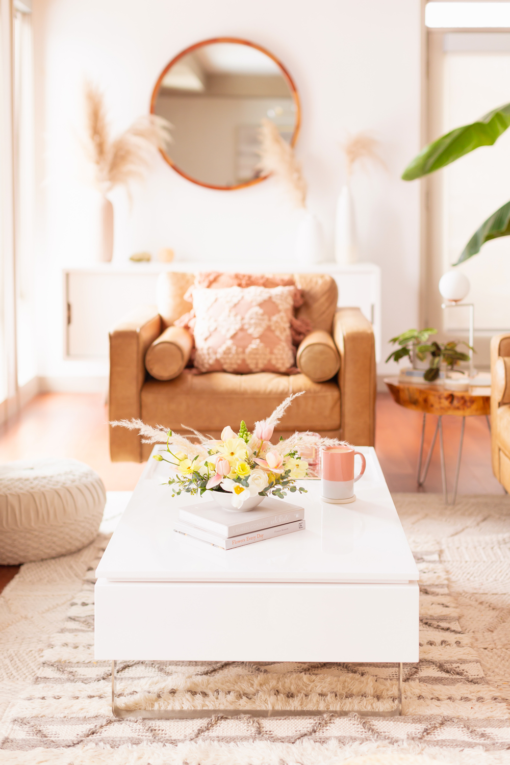 A Pastel Easter Flower Arrangement featuring pampas grass on white coffee table with a pink mug in bright and airy mid century meets boho living room | Calgary Lifestyle Blogger // JustineCelina.com