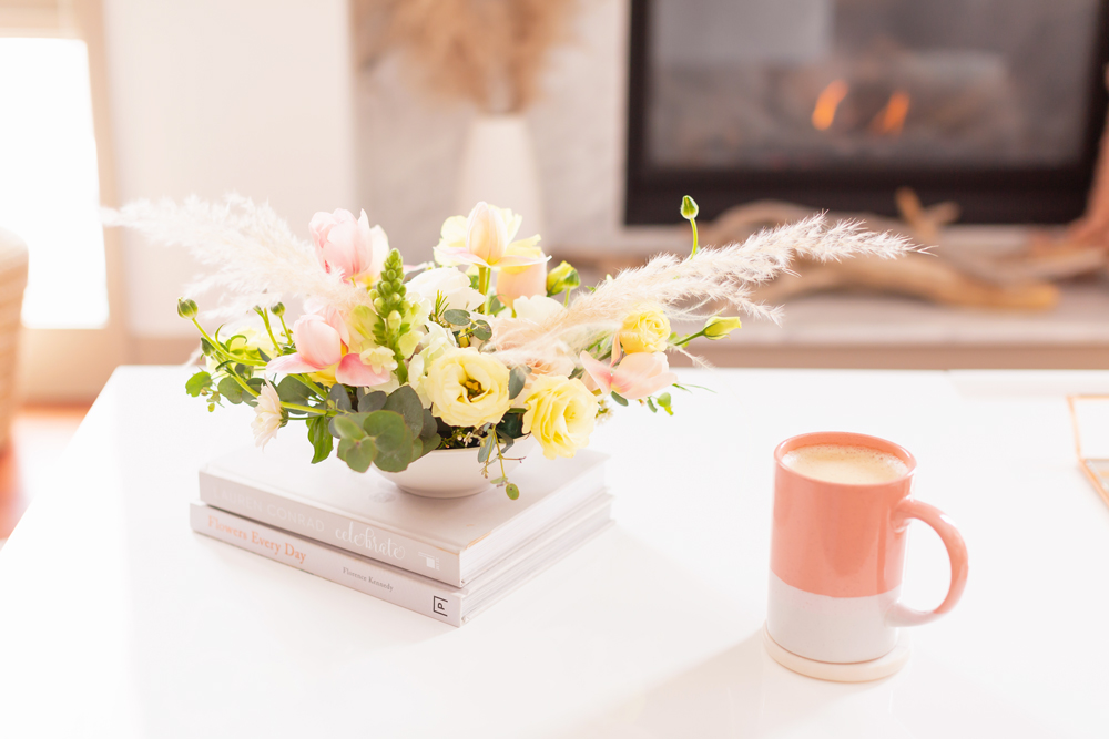 An easter flower arrangement with pampas grass on white coffee table with a pink mug in front of a white marble fireplace | Calgary Lifestyle Blogger // JustineCelina.com