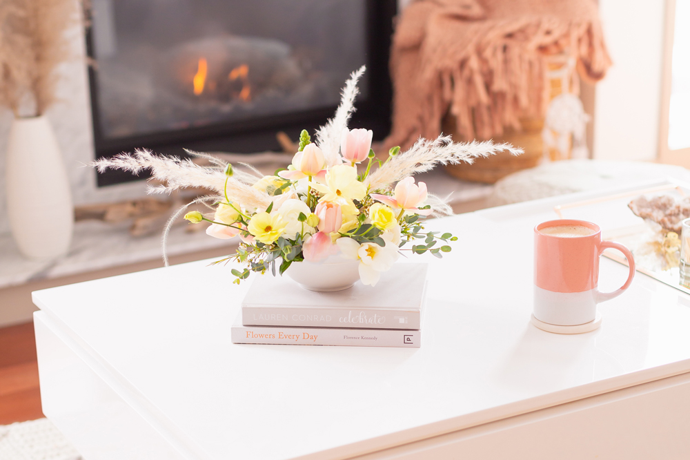 A cheerful spring flower arrangement with pampas grass on white coffee table with a pink mug in front of a white marble fireplace | Calgary Lifestyle Blogger // JustineCelina.com