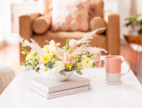 A Pastel Easter Flower Arrangement featuring Quicksand and Spray Roses, Ranunculus and Butterfly Ranunculus, Tulips, Hyacinths, Lisianthus, Eucalyptus, Wax Flowers and Pampas Grass on white coffee table with a pink mug in bright and airy boho living room | Calgary Lifestyle Blogger // JustineCelina.com