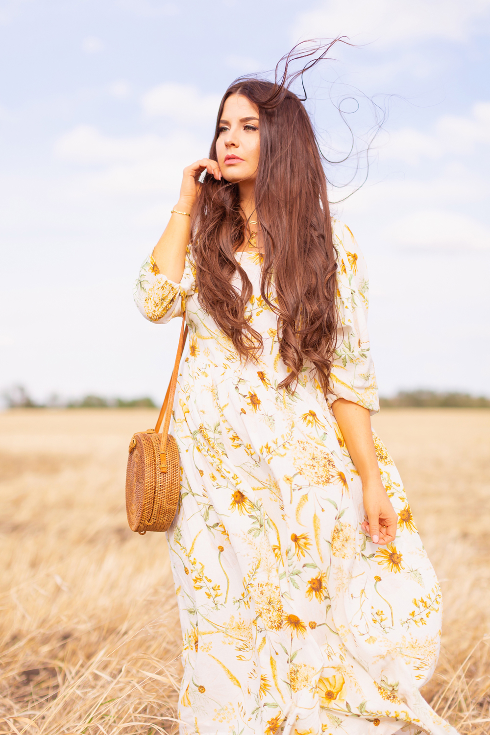 H&M Wildflower Collection Review | Brunette woman wearing a H&M A Meadow of Wildflowers Collection Long Crinkled Dress and a Balinese round rattan bag in a wheat field in the wind | H&M Wildflower Collection Canada | H&M Wildflower Collection Canada | Spring/Summer 2021 Trends | The Best Cotton Dresses 2021 | Boho Spring / Summer Outfit Ideas | Alberta Wildflower Field | Cottage Core Fashion | Cottagecore Outfits | Calgary Creative Lifestyle & Fashion Blogger // JustineCelina.com