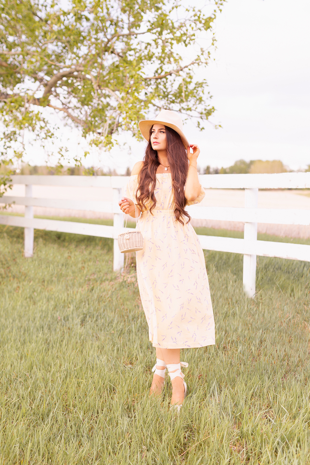 H&M Wildflower Collection Review | Brunette woman wearing a H&M A Meadow of Wildflowers Collection Off-the-shoulder Dress with a woven fedora, straw basket bag and cream espadrilles on an acreage with a white fence | H&M Wildflower Collection Canada | H&M Wildflower Collection Canada | Spring/Summer 2021 Trends | The Best Cotton Dresses 2021 | The Best H&M Dresses Summer 2021 | Alberta Wildflower Field | Cottage Core Fashion | Calgary Creative Lifestyle & Fashion Blogger // JustineCelina.com