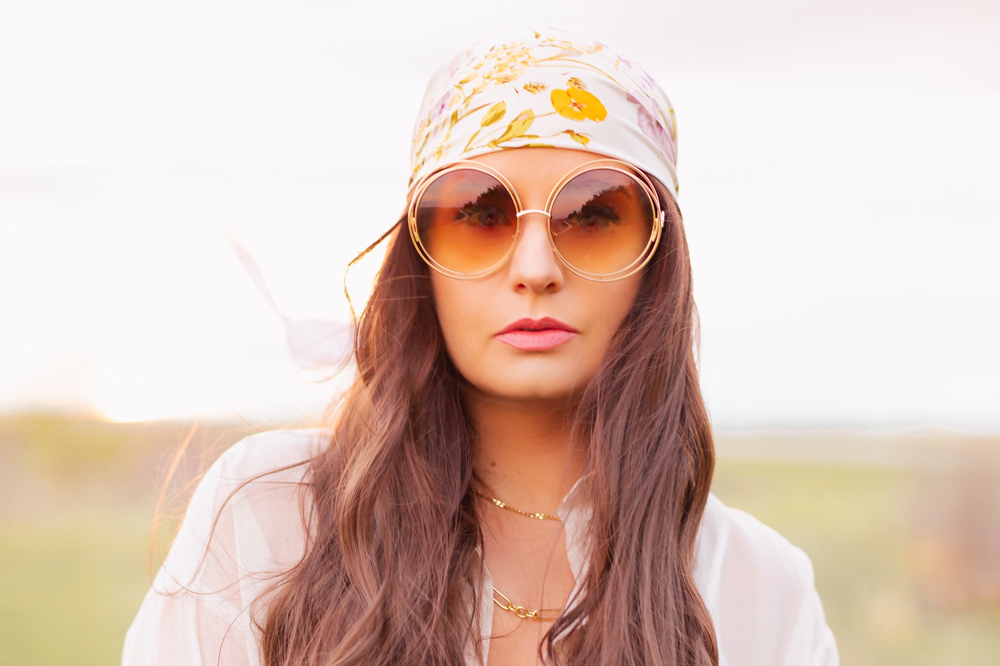 H&M Wildflower Collection Review | Brunette woman wearing a H&M A Meadow of Wildflowers Collection Patterned Satin Scarf on her head with flowy white cotton dress, airy button down shirt and oversized sunglasses in a field at sunset | H&M Wildflower Collection Canada | H&M Wildflower Collection Canada | Spring/Summer 2021 Trends | The Best Cotton Dresses 2021 | Boho Spring / Summer Outfit Ideas | Calgary Creative Lifestyle & Fashion Blogger // JustineCelina.com