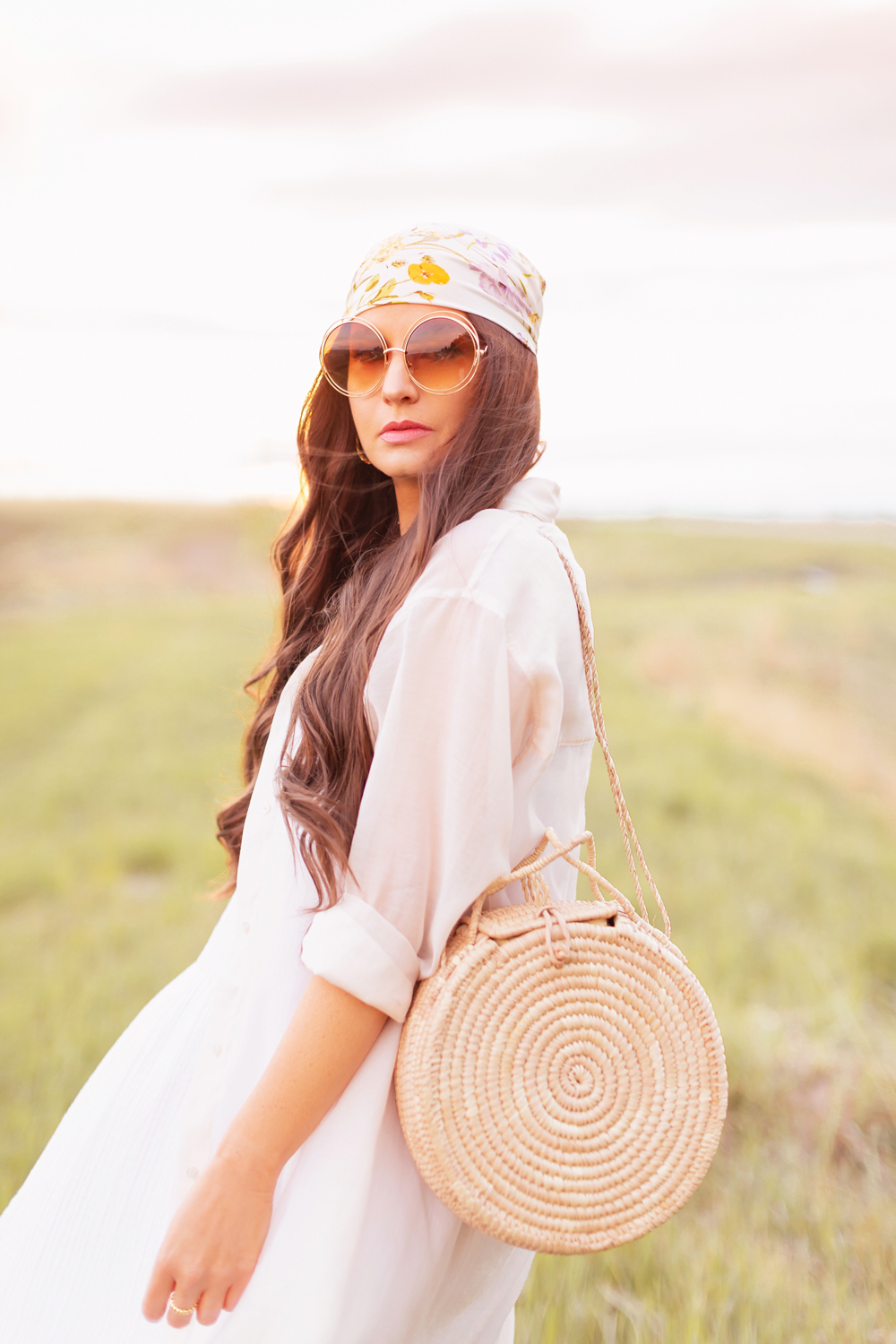 H&M Wildflower Collection Review | Brunette woman wearing a H&M A Meadow of Wildflowers Collection Patterned Satin Scarf on her head with flowy white cotton dress, airy button down shirt, natural material bag and oversized sunglasses in a field at sunset | H&M Wildflower Collection Canada | H&M Wildflower Collection Canada | Spring/Summer 2021 Trends | The Best Cotton Dresses 2021 | Boho Spring / Summer Outfit Ideas | Calgary Creative Lifestyle & Fashion Blogger // JustineCelina.com