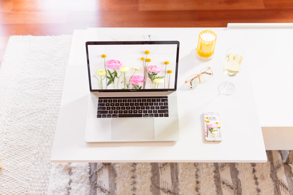 DIGITAL BLOOMS JULY 2021 | 11 Free Downloadable Floral Tech Backgrounds for Summer | Feminine WFH set up with a MacBook Pro and iPhone featuring JustineCelina'sJuly Digital Blooms floral tech wallpaper, a glass of white wine and a yellow candle in a bright and sunny bohemian Living Room | Female Entrepreneur Digital Wallpapers | The Best of Justine Celina's Summer Digital Blooms | Summer Flower Desktop Wallpaper | Calgary Creative Lifestyle Blogger // JustineCelina.com