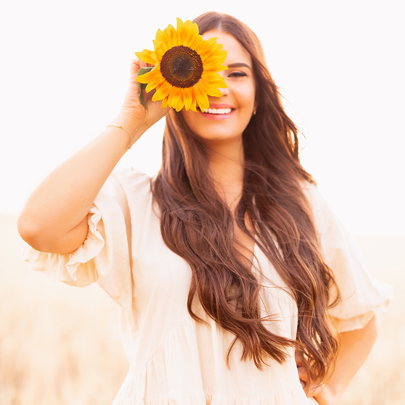 Meet Justine // Justine Celina Maguire | Calgary Lifestyle Blogger | Justine Celina Maguire's Country Garden Sunflowers | JustineCelina Sunflower Portrait | Brunette woman wearing a cream linen dress holding a sunflower over her eye and smiling in a barley field at golden hour | Calgary, Alberta, Canada Creative Lifestyle Blogger and Entrepreneur // JustineCelina.com